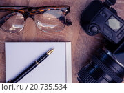 Купить «Pen on paper by camera and eye glasses at table», фото № 20735534, снято 12 июня 2015 г. (c) Wavebreak Media / Фотобанк Лори