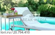 Купить «Breakfast set up by the pool», видеоролик № 20794410, снято 20 апреля 2018 г. (c) Wavebreak Media / Фотобанк Лори