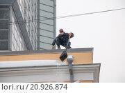 Гастарбайтер без страховки сбрасывает лопатой снег с крыши (2016 год). Редакционное фото, фотограф Александр Михайловский / Фотобанк Лори