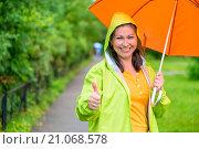 Купить «Веселая девушка стоит под зонтом и показывает большой палец руки вверх», фото № 21068578, снято 1 августа 2015 г. (c) Константин Лабунский / Фотобанк Лори