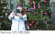Купить «Девушка делает селфи на телефон на фоне елочных украшений на новогодней елке», видеоролик № 21105026, снято 24 января 2016 г. (c) Кекяляйнен Андрей / Фотобанк Лори
