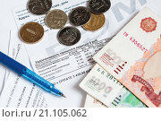 Купить «Российские деньги и шариковая ручка лежат на квитанциях на оплату коммунальных услуг», эксклюзивное фото № 21105062, снято 25 января 2016 г. (c) Игорь Низов / Фотобанк Лори