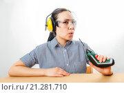 Купить «Девушка в наушниках и очках сидит за столом и дует на дрель», фото № 21281710, снято 20 января 2016 г. (c) Mark Agnor / Фотобанк Лори