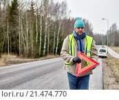Купить «Mid adult man wearing reflector vest and he have a red warning triangle - road and vehicle on background.», фото № 21474770, снято 22 декабря 2014 г. (c) easy Fotostock / Фотобанк Лори