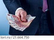 Купить «Мужчина в классическом костюме держит российские банкноты», фото № 21664750, снято 23 декабря 2015 г. (c) Pavel Biryukov / Фотобанк Лори