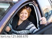 Купить «Happy mature woman sitting in new car», фото № 21668670, снято 21 декабря 2015 г. (c) Яков Филимонов / Фотобанк Лори