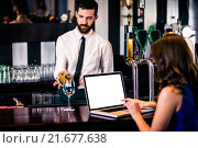 Купить «Barman giving a drink to customer using laptop», фото № 21677638, снято 25 сентября 2015 г. (c) Wavebreak Media / Фотобанк Лори