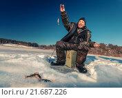 Купить «Счастливый рыбак поймал рыбу на зимней рыбалке», фото № 21687226, снято 21 января 2014 г. (c) Михаил Дударев / Фотобанк Лори