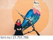 Купить «Молодая девушка стоит возле стены с рисунком птицы», эксклюзивное фото № 21701786, снято 17 апреля 2015 г. (c) Игорь Низов / Фотобанк Лори