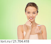smiling young woman applying lip balm to her lips. Стоковое фото, фотограф Syda Productions / Фотобанк Лори