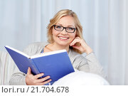 Купить «smiling woman reading book and sitting on couch», фото № 21704678, снято 27 ноября 2015 г. (c) Syda Productions / Фотобанк Лори