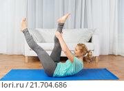 Купить «woman exercising on mat at home», фото № 21704686, снято 27 ноября 2015 г. (c) Syda Productions / Фотобанк Лори