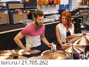 Купить «happy man and woman playing cymbals at music store», фото № 21705262, снято 11 декабря 2014 г. (c) Syda Productions / Фотобанк Лори