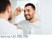 Купить «man with tweezers tweezing eyebrow at bathroom», фото № 21705750, снято 15 января 2016 г. (c) Syda Productions / Фотобанк Лори