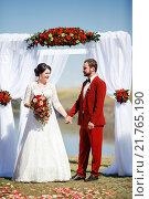 Купить «Невеста и жених стоят возле арки», фото № 21765190, снято 30 августа 2015 г. (c) Евгений Майнагашев / Фотобанк Лори