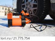 Автомобильный компрессор воздуха на фоне колеса машины. Стоковое фото, фотограф Евгений Майнагашев / Фотобанк Лори