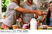 Купить «Smiling friends having breakfast», видеоролик № 21776990, снято 23 июля 2019 г. (c) Wavebreak Media / Фотобанк Лори