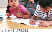 Купить «Cute siblings drawing on a notebook in the living room», видеоролик № 21778022, снято 28 января 2020 г. (c) Wavebreak Media / Фотобанк Лори