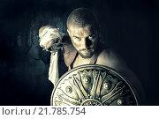Купить «Gladiator posing with shield and sword in a dark background», фото № 21785754, снято 20 сентября 2019 г. (c) PantherMedia / Фотобанк Лори