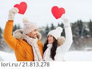 Купить «happy couple with red hearts over winter landscape», фото № 21813278, снято 23 января 2016 г. (c) Syda Productions / Фотобанк Лори