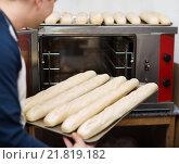 Купить «Smiling cheerful handsome man baking baguettes», фото № 21819182, снято 19 сентября 2018 г. (c) Яков Филимонов / Фотобанк Лори