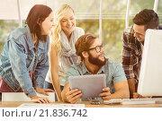 Composite image of happy business people using digital tablet at computer desk. Стоковое фото, агентство Wavebreak Media / Фотобанк Лори