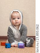 Ребенок сидит на полу в сером костюме и смотрит в камеру. Стоковое фото, фотограф Ирина Столярова / Фотобанк Лори
