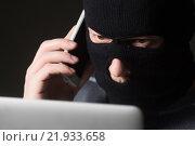 Купить «Хакер в маске сидит перед ноутбуком и разговаривает по мобильному», фото № 21933658, снято 19 февраля 2016 г. (c) Mark Agnor / Фотобанк Лори