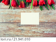 Купить «close up of red tulips and blank paper or letter», фото № 21941010, снято 3 марта 2015 г. (c) Syda Productions / Фотобанк Лори