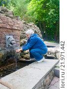 Купить «Пожилая седая женщина набирает святую воду в ладошки. Поселок городского типа Красный ключ, Нижнекамский район, Татарстан. Святой Ключ», эксклюзивное фото № 21971442, снято 20 августа 2015 г. (c) Наталья Федорова / Фотобанк Лори
