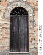 Купить «Черная деревянная дверь с аркой в старой каменной стене», фото № 21975322, снято 11 февраля 2016 г. (c) EugeneSergeev / Фотобанк Лори