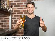 Купить «Handsome man holding a pint of beer with thumbs up», фото № 22001550, снято 24 октября 2015 г. (c) Wavebreak Media / Фотобанк Лори