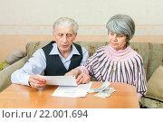 Купить «Пожилые мужчина и женщина изучают на счета по коммунальным платежам», фото № 22001694, снято 27 февраля 2016 г. (c) Юлия Кузнецова / Фотобанк Лори