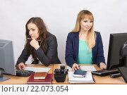 Две сотрудницы офиса работают в компьютере за одним рабочим столом. Стоковое фото, фотограф Иванов Алексей / Фотобанк Лори
