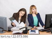 Девушки коллеги в офисе, одна работает с бумажными документами, вторая в компьютере с электронными. Стоковое фото, фотограф Иванов Алексей / Фотобанк Лори