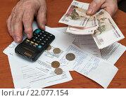 Купить «Пожилой мужчина подсчитывает на калькуляторе расходы на оплату коммунальных услуг», эксклюзивное фото № 22077154, снято 3 марта 2016 г. (c) Игорь Низов / Фотобанк Лори