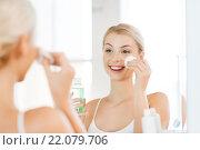 Купить «young woman with lotion washing face at bathroom», фото № 22079706, снято 13 февраля 2016 г. (c) Syda Productions / Фотобанк Лори