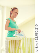 Купить «happy woman with iron and ironing board at home», фото № 22080210, снято 25 января 2015 г. (c) Syda Productions / Фотобанк Лори