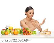 Купить «woman with fruits rejecting hamburger», фото № 22080694, снято 12 января 2013 г. (c) Syda Productions / Фотобанк Лори