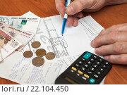Купить «Подорожание коммуналки. Руки старика обводят итоговую сумму в квитанции на оплату коммунальных услугх», эксклюзивное фото № 22104450, снято 3 марта 2016 г. (c) Игорь Низов / Фотобанк Лори