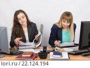 Две сотрудницы офиса сидят за одним рабочим столом и работают с бумагами и документами. Стоковое фото, фотограф Иванов Алексей / Фотобанк Лори