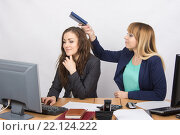 Офисная работница исподтишка собирается ударить по голове коллегу блокнотом. Стоковое фото, фотограф Иванов Алексей / Фотобанк Лори