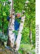 Купить «Улыбающаяся пожилая женщина выглядывает  из-за ствола березы», фото № 22125526, снято 20 августа 2015 г. (c) Наталья Федорова / Фотобанк Лори