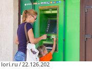 Анапа, Россия - 20 сентября 2015 года: Молодая девушка с ребенком снимают деньги с банкомата сбербанка. Редакционное фото, фотограф Иванов Алексей / Фотобанк Лори
