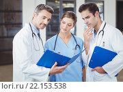 Купить «Doctors examining while holding clipboard», фото № 22153538, снято 1 ноября 2015 г. (c) Wavebreak Media / Фотобанк Лори