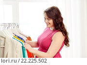 Купить «happy plus size woman choosing clothes at wardrobe», фото № 22225502, снято 21 февраля 2016 г. (c) Syda Productions / Фотобанк Лори