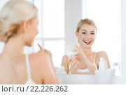 Купить «happy woman applying cream to face at bathroom», фото № 22226262, снято 13 февраля 2016 г. (c) Syda Productions / Фотобанк Лори