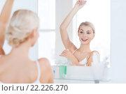 Купить «woman with antiperspirant deodorant at bathroom», фото № 22226270, снято 13 февраля 2016 г. (c) Syda Productions / Фотобанк Лори