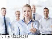 Купить «smiling businesswoman showing thumbs up in office», фото № 22226598, снято 25 октября 2014 г. (c) Syda Productions / Фотобанк Лори