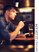 Купить «man drinking beer and smoking cigarette at bar», фото № 22226634, снято 22 апреля 2015 г. (c) Syda Productions / Фотобанк Лори